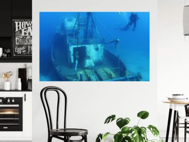 Scuba Divers Exploring underwater ship wreck