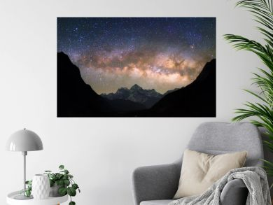 "Bowl of Heavens. Bright and vivid Milky Way galaxy over the snowy mountains. Beautiful starry night sky seems to be in a ""bowl"" between the silhouetted hills."