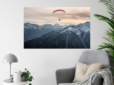 Paraglider flight over the snow-capped peaks of the Caucasus mountains