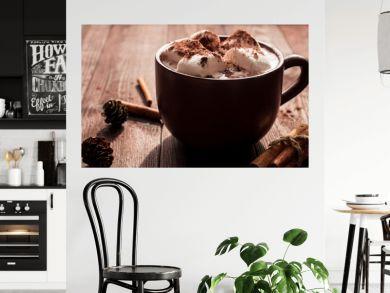 Hot chocolate in a mug, marshmallows, cinnamon sticks and fir cones, close-up