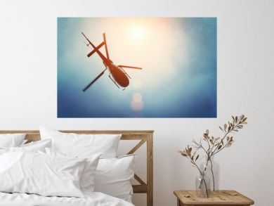 Helicopter flying in the blue sky with sun