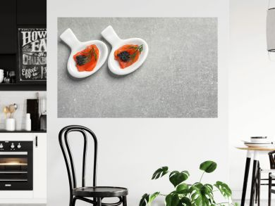 Tasty appetizers with black caviar and salmon on grey background