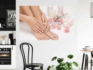 The picture of ideal done manicure and pedicure. Female hands and legs in the spa spot.