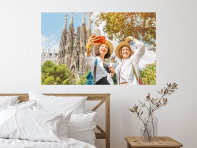 BARCELONA, SPAIN - 11 JULY 2018: Young girls friends making selfie photo on her smartphone in front of the famous Sagrada Familia catholic cathedral. Travel in Barcelona concept