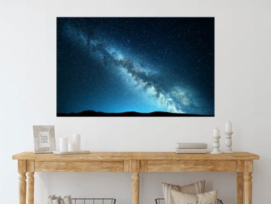 Night landscape with amazing Milky Way at mountains. Blue night starry sky with hills at summer. Beautiful Galaxy. Universe. Space background