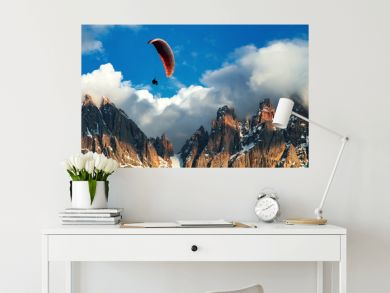 Paraglider flying near high mountains. Dolomites, Italy