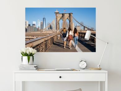 Three girls walking on the Brooklyn Bridge with the New York skyline on the back