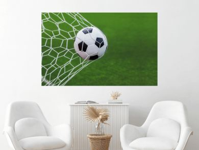soccer ball in goal with green backgroung