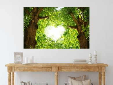 Silhouette of a heart in the foliage of trees poplar. Two beautiful textured tree trunks with green juicy leaves in the rays of sunlight.