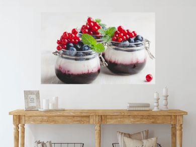 Italian dessert panna cotta with berry sauce in glass jars