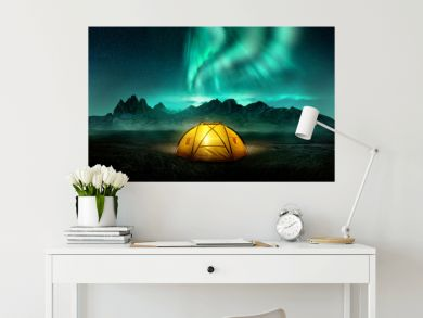 A glowing yellow camping tent under a beautiful green northern lights aurora. Travel adventure landscape background. Photo composite.