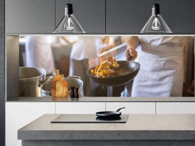 Mid section of chef cooking in kitchen stove