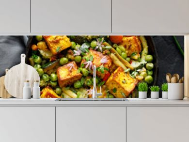 Tofu with vegetables sprinkled with herbs and edible flowers, top view. Vegan dish delicious and nutritious. Healthy eating concept