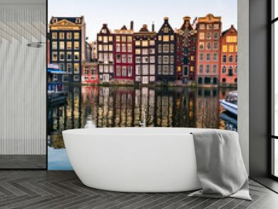 View of colorful facades of typical Amsterdam houses reflecting in the Amstel river canal in Amsterdam during sunset
