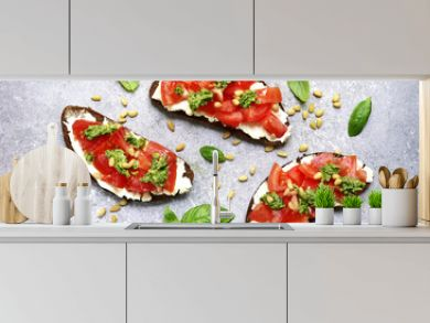 Rye toasts with soft cheese, tomatoes, pine nuts and pesto sauce. Top view with copy space.