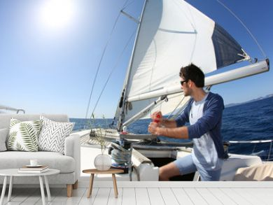 Man sailing with sails out on a sunny day