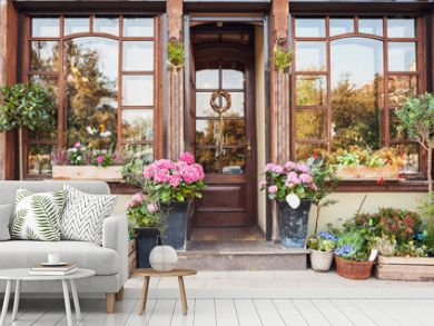 Flower store or cafe entrance decorated with flowers. Rustic style concept. Beautiful design elements