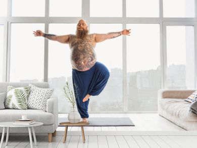 Tattooed man practicing yoga at home