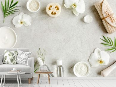 Spa treatment concept. Natural/Organic spa cosmetics products, sea salt, massage brush, tropic palm leaves on gray marble table from above. Spa background with a space for a text, flat lay, top view