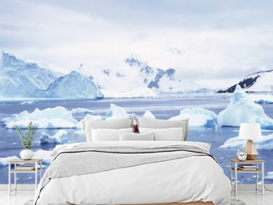 Panoramic view of ecological tourists in inflatable Zodiac boat with glaciers and icebergs in Paradise Harbor, Antarctica
