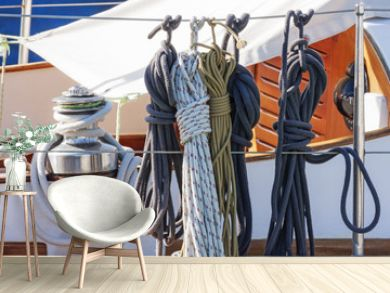 Colorful nautical accessories with ropes, pulley and chromed winch on a well equipment wooden sailboat