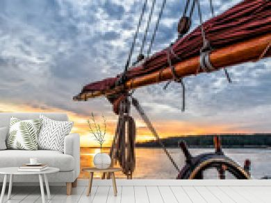 Sunrise at sea on a tall ship classic sailboat. Close up of the wheel, boom and stern against a dramatic sky, clouds and the gold light of dawn reflected in the water.