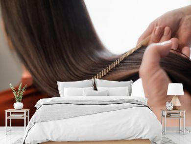Close up of hairdresser making hair styling for woman while combing by hairbrush