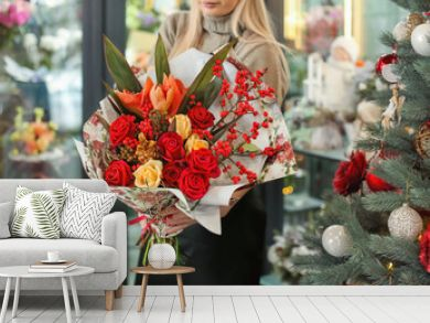 Female florist holding beautiful bouquet in flower shop
