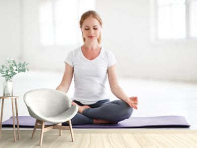 woman practicing yoga and meditating in lotus position
