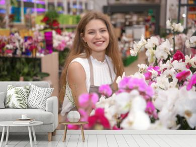 Beautiful female florist with orchids in  flower shop