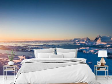 Sunset panoramic view of snow covered Antarctic land. Picturesque South Pole scenery. Beauty of the untouched nature. The wilderness landscape. Travel background. Holiday, hiking, sport, recreation