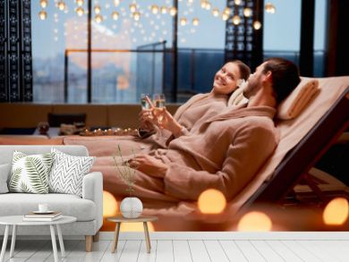 Spa, relax, enjoying concept. Married couple together relaxing in spa salon, lying on beds drinking champagne, using candles