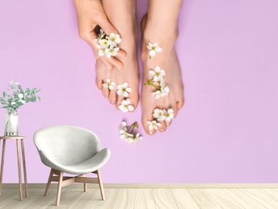 Beautiful female feet, healthy pedicure, well-groomed nails. Flowers on legs, skin care concept.