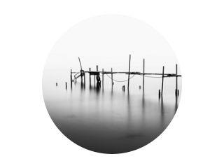 Een lange blootstelling van een verwoeste pier in het midden van de zee. Verwerkt in zwart-wit.