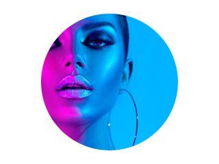 Mannequin brunette vrouw in kleurrijke felle neonlichten poseren in studio. Mooi sexy meisje, trendy gloeiende make-up, metallic zilveren lippen