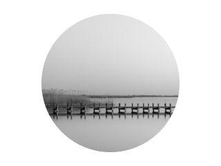Grijswaardenopname van een houten pier bij de zee overdag