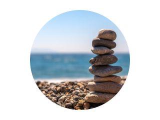 compositie maken door stenen te stapelen aan zee