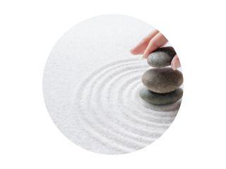 Hand stapelen zen stenen op de zand wellness-achtergrond