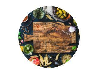 Italiaans eten kookingrediënten op donkere achtergrond met rustieke houten snijplank in het midden, bovenaanzicht, kopieerruimte