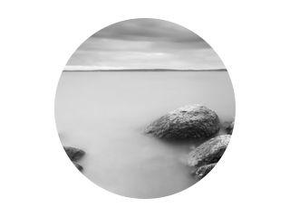 Stenen in water over zonsondergang, langdurig blootstellingseffect.