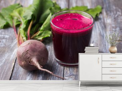 Fresh beet juice in glasses with a straw on a wooden background, selective focus. Healthy detox diet