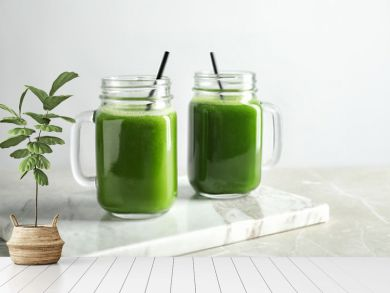 Mason jars with delicious detox juice on table