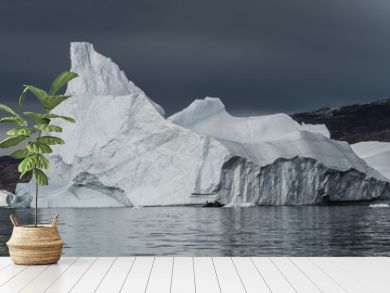 rubber dinghy cruising in front of massive Icebergs floating in the fjord scoresby sund, east Greenland