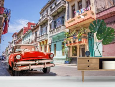 Vintage classic red american car in a colorful street of Havana, Cuba.
