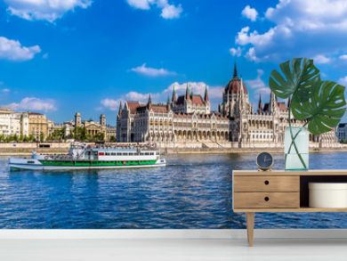 A ferry boat passes along the eastern shore of the River Danube in Budapest past the Parliament building in the summertime