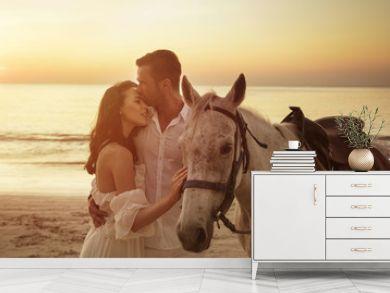 Young couple walking a majestic horse - seaside landscape