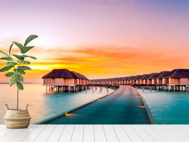 Amazing sunset panorama at Maldives. Luxury resort villas seascape with soft led lights under colorful sky. Beautiful twilight sky and colorful clouds. Beautiful beach background for vacation holiday